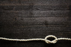 Natural rope with knot on dark wood Royalty Free Stock Photo