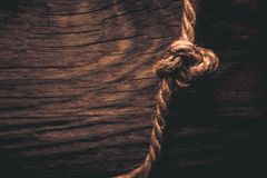 Natural rope on a wooden rustic texture for background. Rough we. Athered wooden board. Toned royalty free stock images