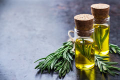 Natural rosemary essential oil for beauty and spa. Healthy lifestyle concept. Natural rosemary essential oil on a rusty black table for beauty, spa, therapy Stock Image