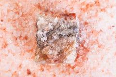 Natural rough Halite mineral in pink Salt close up. Top view of natural rough Halite mineral in grained pink Himalayan Salt close up royalty free stock photos