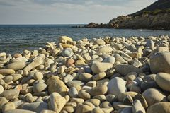 Natural round pebbles on the beach. Detail of some white pebbles on a typical beach of the southern coast of southern Sardinia in Italy, with the background of royalty free stock photo