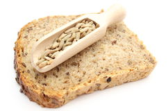 Natural rye grain on wooden spoon and slice of bread Stock Photos