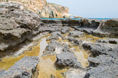 Natural salt pans with water in Comino Island in Malta. Royalty Free Stock Images