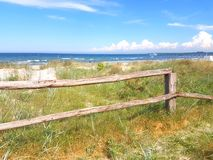 Natural sand dune beach area and fence. Natural sand dune beach area with sea grass and fence royalty free stock photos