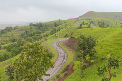 Natural scenery. Road on the hill, to school. greenery on hills, and green tree and field providing natural beauty to the scenery stock images
