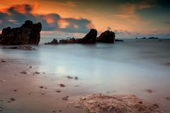 Natural seascape at dawn, Thailand. Dawn seascape with natural stone arch with motion cloud , wave, twilight sky in Rayong beach, Thailand. Big stopper filter stock image