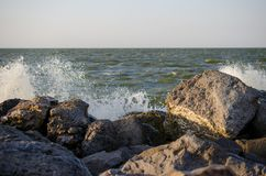Stones on the shore. Natural seashore stones textured surface. Stones on the sea shore. Sea waves crashing against the stones. Azov sea Royalty Free Stock Photography
