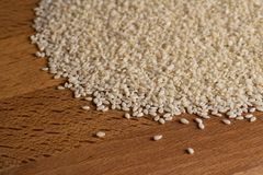 Natural sesame seeds on a wooden board surface. Natural sesame seeds on a wooden board close-up Stock Photography