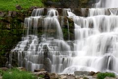 Natural setting of waterfalls cascading over several layers of rock and sediment to the basin below. Gorgeous natural setting with the soothing sound of stock image