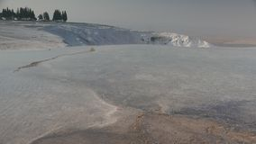 Natural sightseeing of flowing mineral water over white terraces in Pamukkale, Turkey. 4k. Natural sightseeing of flowing mineral water over white limestone stock video footage