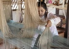 Natural silk farming and handcrafted manufacture of silk artifacts -ladies handweaving ancient patterns in silk on traditional lo stock photography