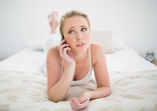 Natural skeptic blonde lying on bed and using smartphone. In bright bedroom Royalty Free Stock Image