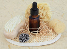 Natural Skincare Products. Aromatherapy essential oil bottle, natural sponges, pumice, nail brush and exfoliating scrub over mottled cream background Stock Image