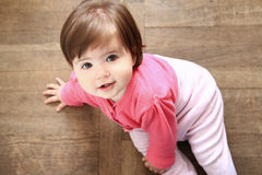 Natural smile. Happy 11 month girl looking up from the wooden floor Royalty Free Stock Photo