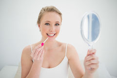 Natural smiling blonde holding mirror and applying lip gloss Royalty Free Stock Image