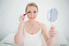 Natural smiling blonde holding mirror and applying mascara Stock Image