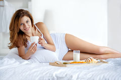 Natural smiling brunette holding a cup of tea in bright bedroom Stock Photography