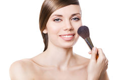 Natural smiling woman and brush on cheek Stock Image