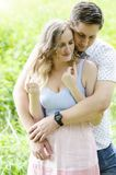 Natural smiling young couple hugging outdoors stock image