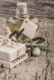Natural soap bar and olive oil bottle on wooden table Stock Photos