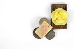 Natural soap bar on round stone and yellow rose candle Royalty Free Stock Photos