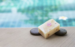 Natural soap bar on stone over blurred swimming pool background Stock Photo