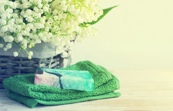 Natural soap of handwork, towel, and spring flowers of a lily of the valley in a wattled basket Royalty Free Stock Image