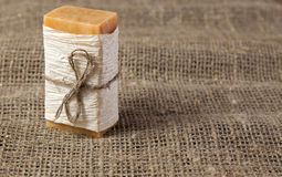 Natural soap on the natural rough fabric. Natural soap with linen ribbon on the natural rough fabric Royalty Free Stock Images