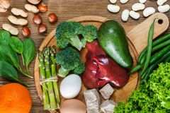 Natural sources of folic acid. As liver, asparagus, broccoli, eggs, salad, avocado, yeast, nuts, spinach, orange and beans Royalty Free Stock Photo