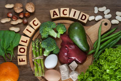 Natural sources of folic acid. As liver, asparagus, broccoli, eggs, salad, avocado, yeast, nuts, spinach, orange and beans Stock Photos