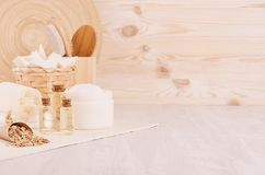 Natural spa massage oil and cosmetics products, bath accessories with bamboo decor on beige wood board, interior. Natural spa massage oil and cosmetics products royalty free stock image