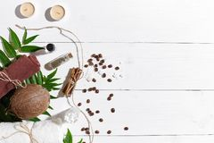 Natural spa set with candles, coffee beans, cinnamon, sea salt, oil, brown towel, coconut and green leaves on white Royalty Free Stock Image