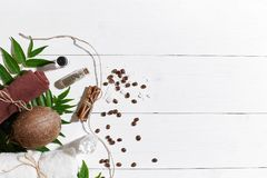 Natural spa set with coffee beans, cinnamon, sea salt, oil, brown towel, coconut and green leaves on white wooden Stock Images