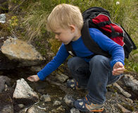 Natural spring water. Little boy (3 years old) drinking from a mountain spring Stock Image