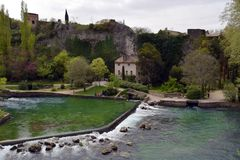 Fontaine-de-Vaucluse, France town pond. Natural spring water gushes from a cave and flows past the historic center in a river lined with parks and shops royalty free stock photo