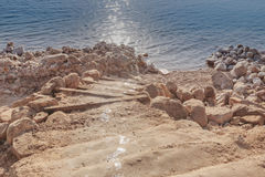 Natural stairway to the stone shore, covered with salt, at the Dead Sea coast. Stock Image
