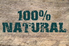 100% Natural  stamped text on old plank Royalty Free Stock Image