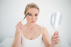 Natural stern blonde holding mirror and using eyebrow brush Stock Photo