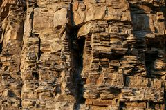 Close-up rufous stony wall with layered uneven hollowed-out surface. Natural stone background. Close-up rufous stony wall with layered uneven hollowed-out Royalty Free Stock Photo