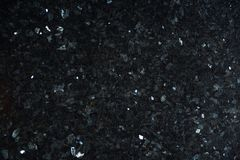 Natural stone of black color with bright sparkles with bluish tint, called labradorite Emerald Pearl stock photography