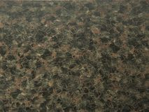 Natural stone granite of black-brown color with dark maroon impregnations. stock images