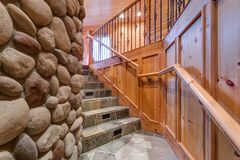 Natural stone staircase leading upstairs. Features wood paneled walls on one side and stone fireplace on the other royalty free stock images