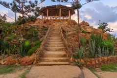 Natural stone stairway with green bushes on both sides leading to wooden pergola with partly cloudy sky in summer time. Natural stone stairway with green bushes Royalty Free Stock Photo