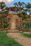 Natural stone stairway with green bushes on both sides leading to wooden pergola with partly cloudy sky at public Park in summer. Natural stone stairway with Stock Photo