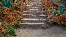 Natural stone stairway with green bushes on both sides at public park in summer time. Natural stone stairway with green bushes on both sides at Montaza Public royalty free stock photography