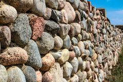 Natural stone wall of round stone, front and back background blurred with bokeh effect stock photos