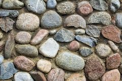 Natural stone wall of round stone, front and back background blurred with bokeh effect royalty free stock images