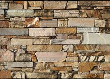Natural stone wall texture background. These stone bricks range in color from white and pink to brown.  Stock Photography