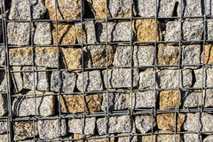 Natural stone wall, versatile in horticulture and slope stabilization; Wire basket filled with broken stones; Buildin  Background. Royalty Free Stock Images