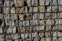 Natural stone wall, versatile in horticulture and slope stabilization; Wire basket filled with broken stones; Buildin  Background. Natural stone wall, versatile Royalty Free Stock Photos